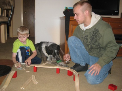 Little Friend and Younger Person building train tracks