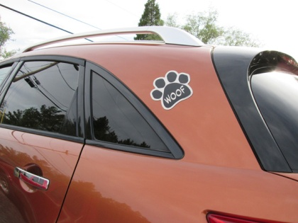 "Magnet paw print on a car that says ""Woof"""