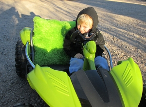 Boy in a lime green toy car