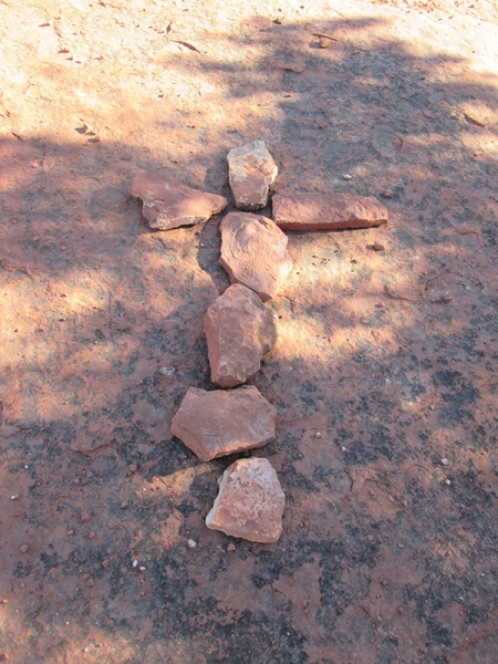 Cross on the ground made of rocks
