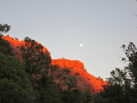 Sugarloaf lit up with the moon above it