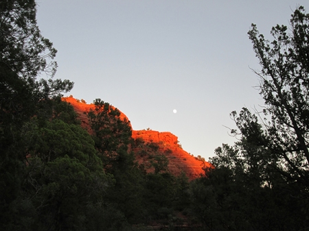 Sugarloaf lit in sunlight with the moon above it